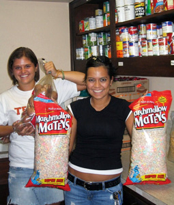Two members of the student organization, Texas Lassos, who volunteer at the Eastside Community Connection food pantry every week helping pack food.