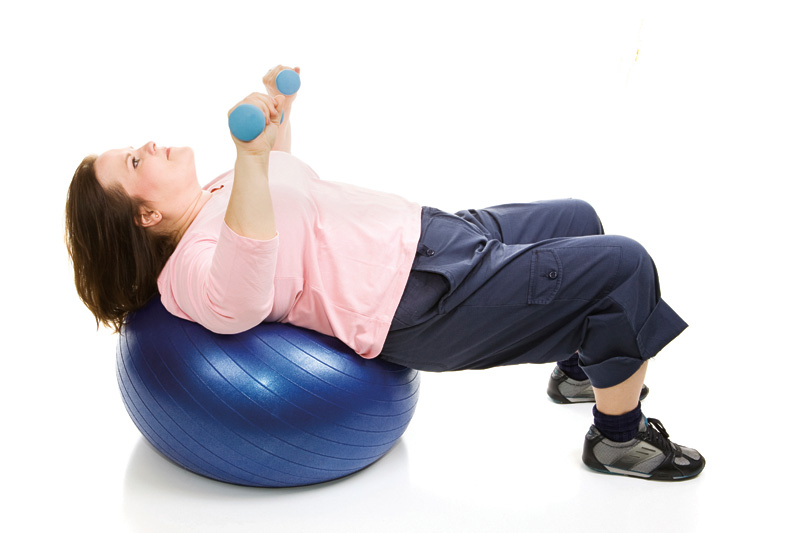 iStock Photo of woman working out with weights on a exercise ball.