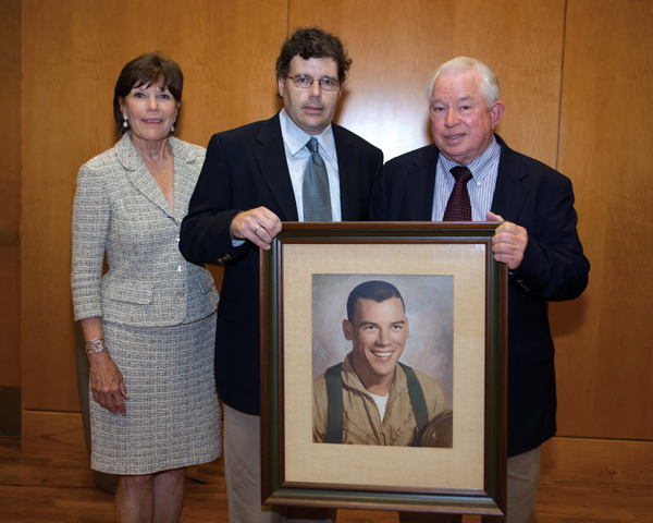 Ellen Temple, John Hurst, Jr., and Jim Hurst displaying Capt. Hurst's portrait.