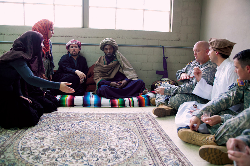 Students from Middle Eastern Studies and Arabic Flagship Programs assume the role of Afghan villagers and translator in a cultural training simulation for officers from the Texas National Guard at Camp Mabry.