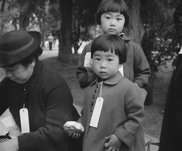 Two children of the Mochida family, with their parents, awaiting bus to a War Relocation center. In 1942, President Roosevelt authorized the relocation and internment of approximately 110,000 Japanese Americans and Japanese who lived along the Pacific coast.