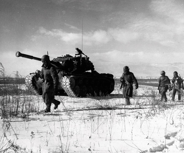 A column of troops and armor of the 1st Marine Division move through communist Chinese lines during their successful breakout from the Chosin Reservoir in North Korea, which began on Nov. 27, 1950. Photo by Corporal Peter McDonaLd, USMC.