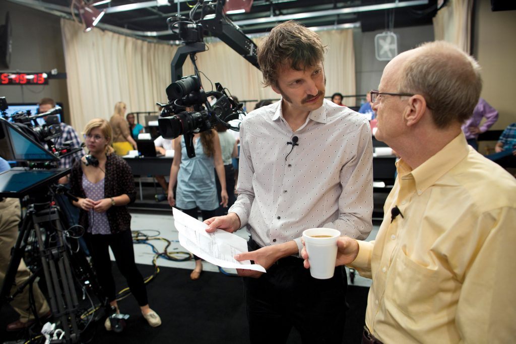 Professors Sam Gosling and Jamie Pennebaker discuss the script before the broadcast begins.