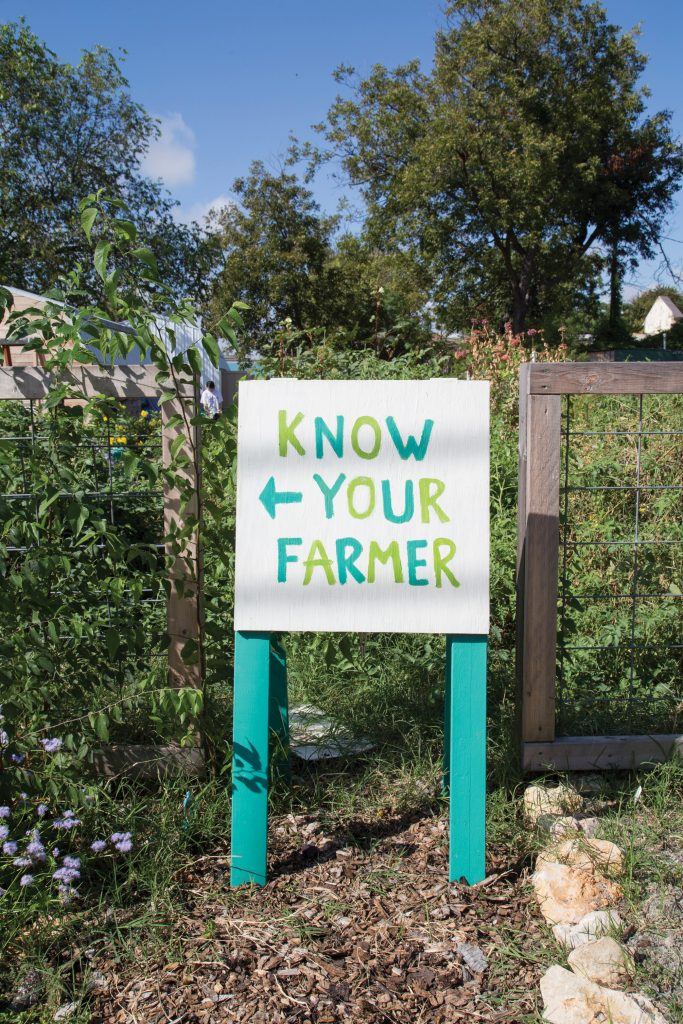 "Sign leading to the community garden reads, ""Know Your Farmer."""