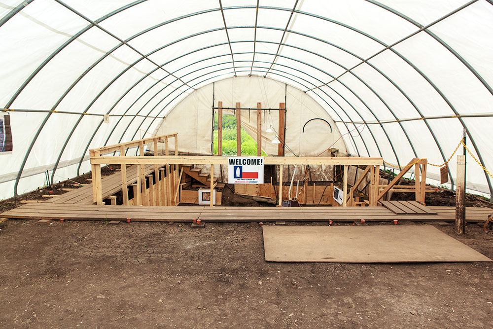 inside of white tent with welcome sign attached to wooden platforms leading down into the Gault dig site.