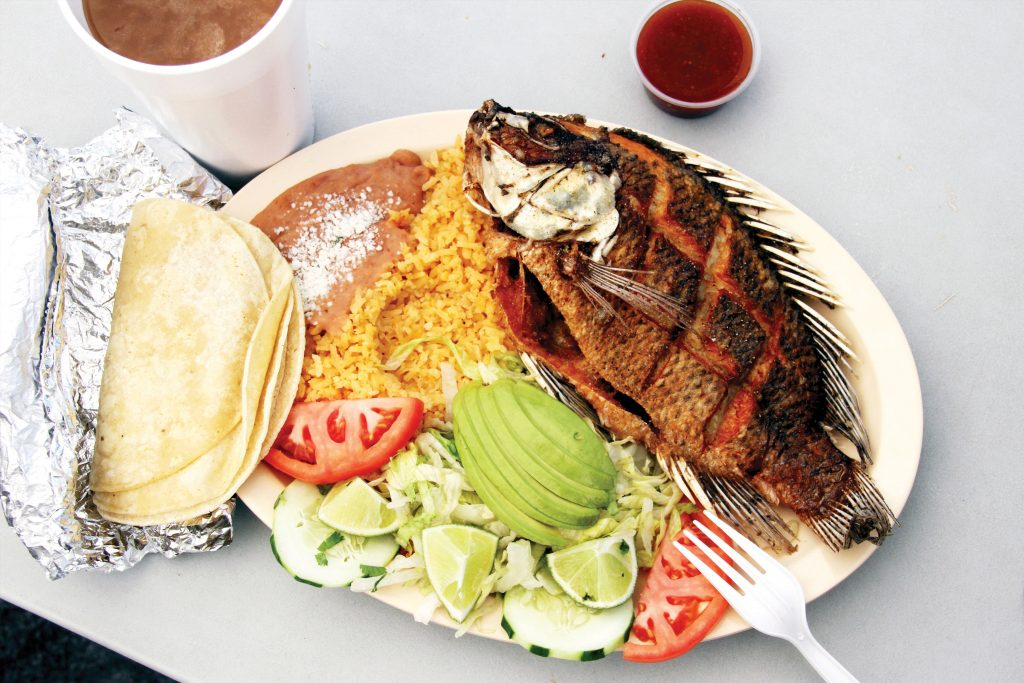 A plate of fish, rice, beans, and vegetables with hot sauce and a drink