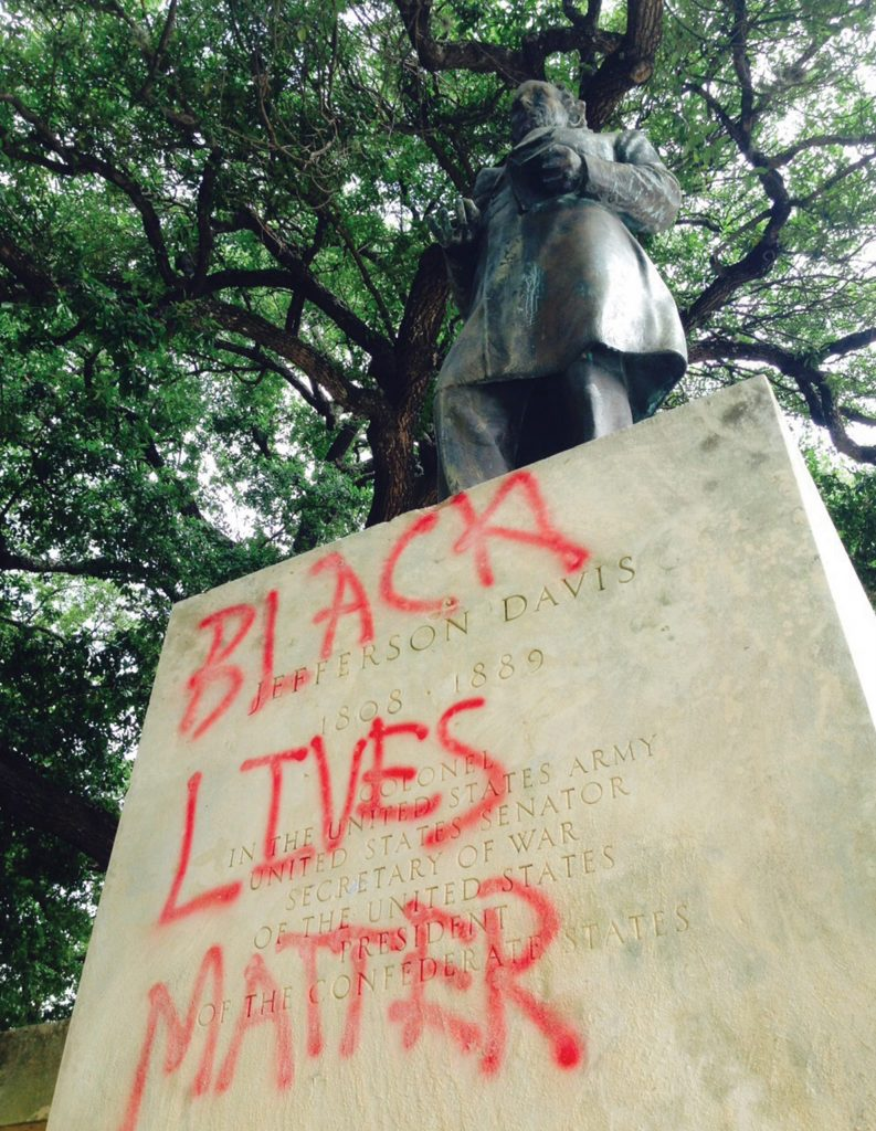 """Photo of the Jefferson Davis statue with """"Black Lives Matter"""" graffiti over the front."""
