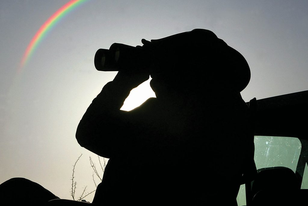 A silhouette of a Minuteman wearing a cowboy hat looking through binoculars. A rainbow is in the clear sky behind him.