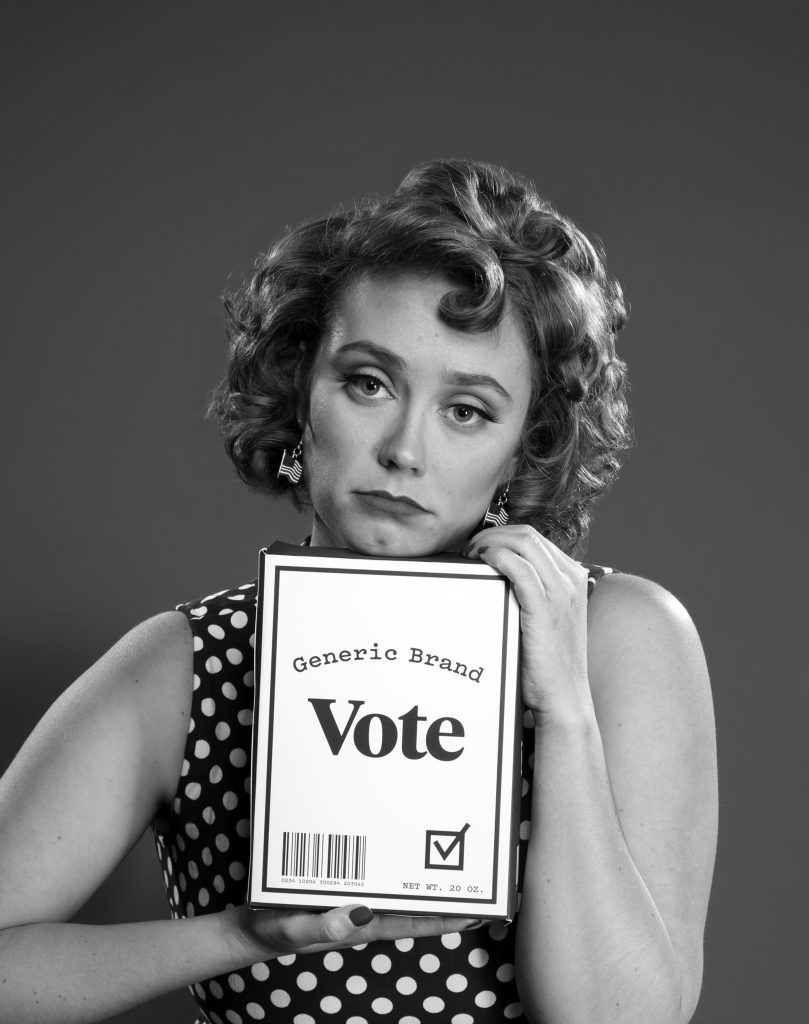 """A tongue-in-cheek black and white photo of a sad-looking woman holding a """"Generic Vote"""" branding box."""