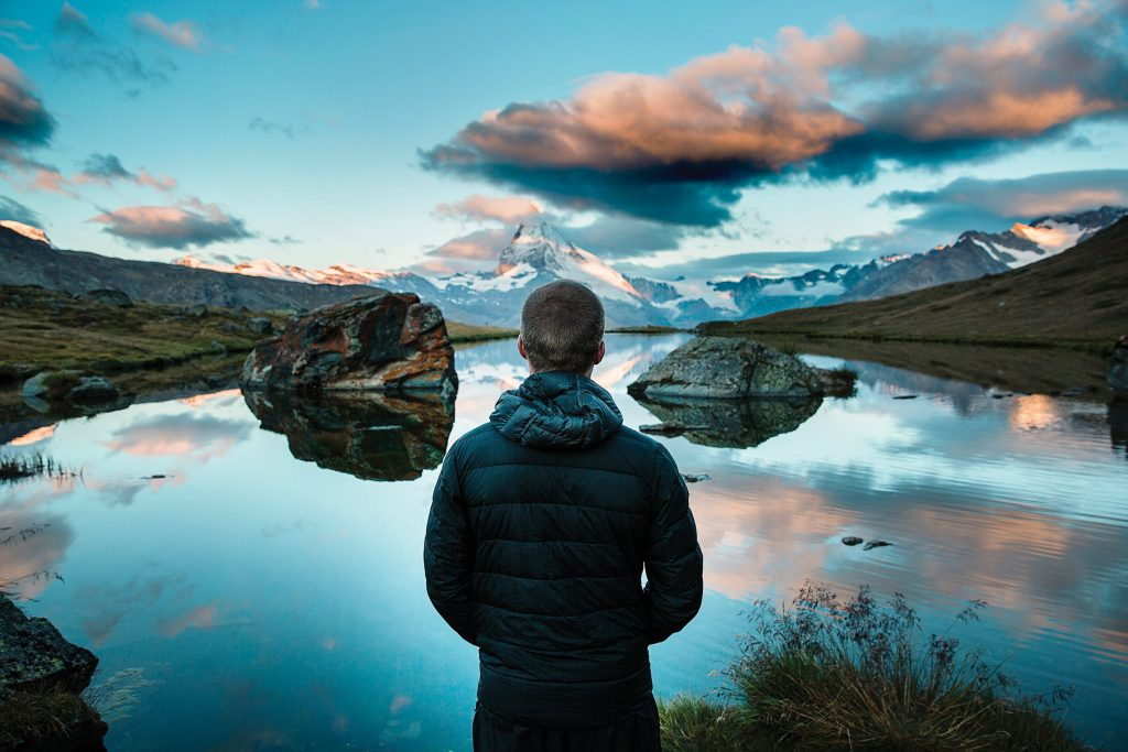 Breathtaking image of a line man looking out towards an impressively clear lake, mountain, and vivid blue sky.