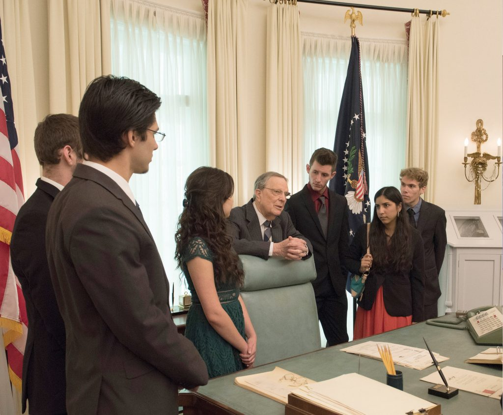 Larry Temple speaks with Larry Temple Scholarship winners during a tour of the LBJ Library Oval Office replica on Jan. 19, 2016.