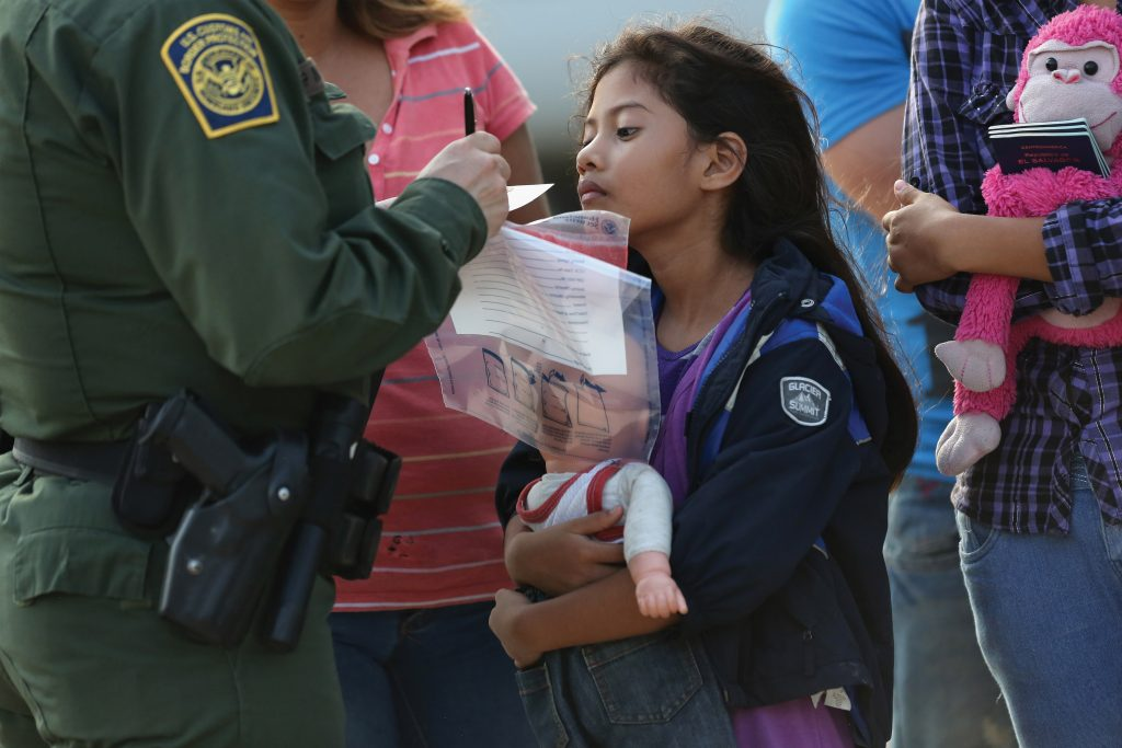 Photo of a young girl holding a doll speaking to a Border Patrol police officer while he takes notes.