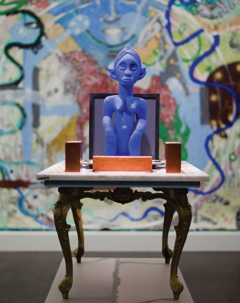 "Photo of Angelbert Metoyer's sculpture, titled ""Everyone Who's Had a Brick Break a Window."" In it, there is an ornate marble table with three brick-like objects along with a purple, wooden figure looking at towards the viewer."