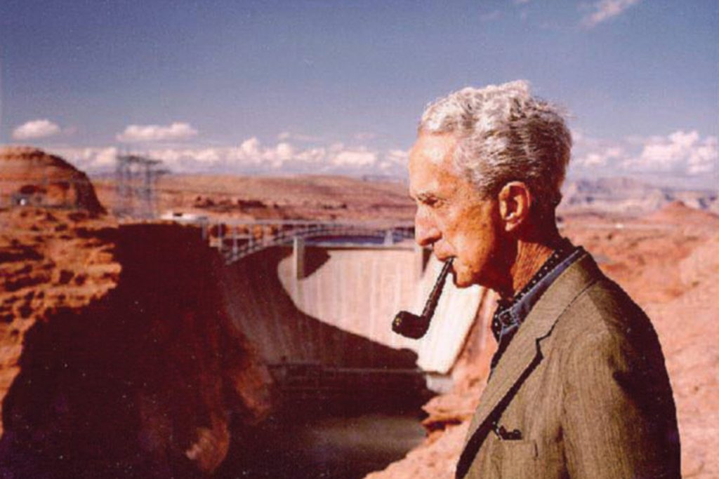 Photo of Norman Rockwell overlooking the Glen Canyon Dam while smoking a pipe.
