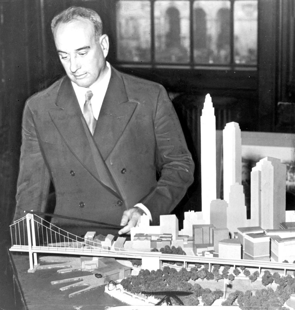 Robert Moses (1888-1981), one of the most powerful urban planners in New York of the mid-20th century, with a model of his proposed Battery Bridge. Ultimately he was forced to settle for a tunnel connecting Brooklyn to Lower Manhattan.