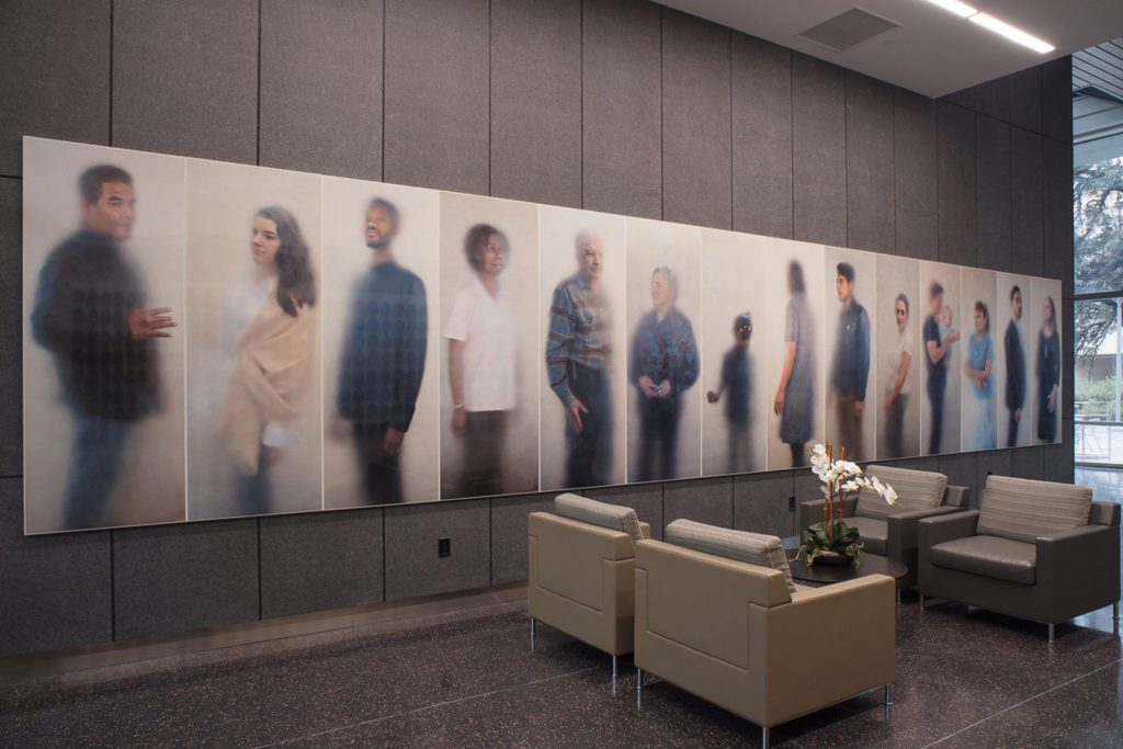 Photo of the lobby of the Dell Medical School. A series of 14 portraits from Ann Hamilton's O N E E V E R Y O N E series hang on the main wall to the entrance.