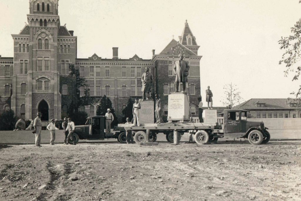Black and white photo of Coppini's statues of Johnston, Reagan and Wilson in front of the old main building.