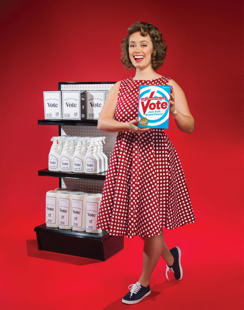 """A tongue-in-cheek photo of a smiling woman holding a brightly branded """"Vote"""" box against a red background. The box reads, """"The Campaign for Your Vote: Just Add Brand Power!"""" (America's Choice). She is steping towards the camera and behind her is a supermarket shelf of """"Generic Branded"""" black and white boxes."""