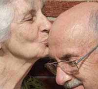 An older woman kissing the bald head of an older man