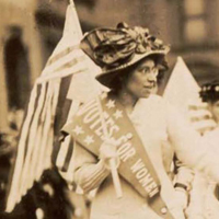 A suffragist marches in a protest parade