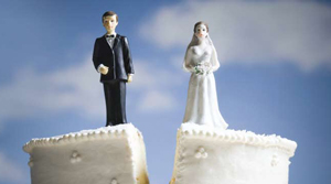 Bride and groom figurines on top of a wedding cake that is splitting apart