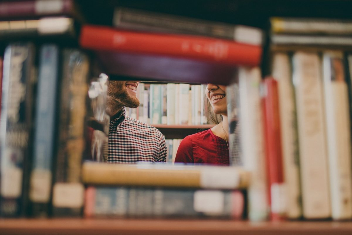 Faces of man and woman smiling at each other behind bookshelf.