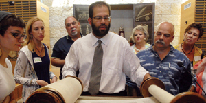 Bible teachers look at a Torah scroll with Rabbi Neil Blumofe at Congregation Agudas Achim in Austin