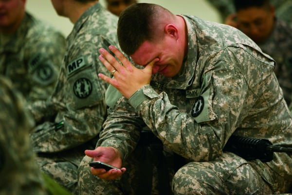 Nathan Bissonnette of the 89th MP Brigade wipes his eyes after talking to his wife on his cell phone
