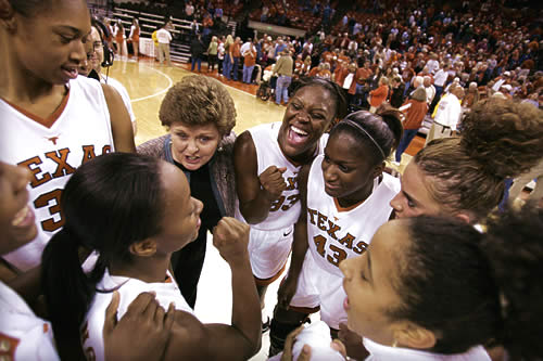 A group of women college basketball players and their coach in a huddle with the court and fans in the background