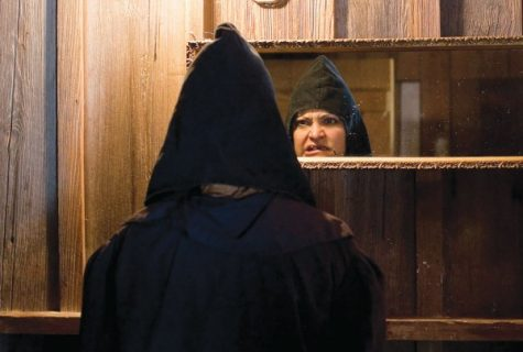 man facing mirror in black pointed hood