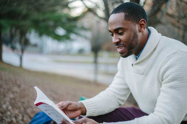 Man reading book outdoors.