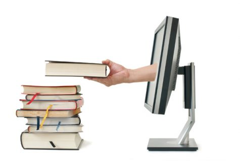 hand reaching out from monitor to place book on top of stack of books