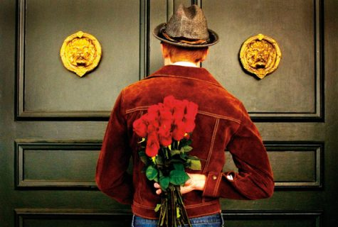 man in hat and red jacket waiting at door with roses behind his back
