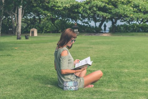 Woman with sunglasses sitting on grass reading book.