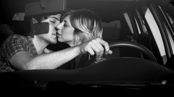 black and white photo of man and woman kissing in a car