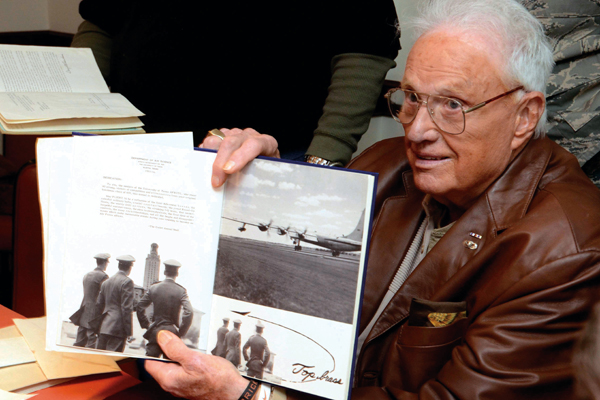 Frank Denius displaying photographs inside a 1956 Air Force ROTC yearbook. Photo by Marsha Miller.