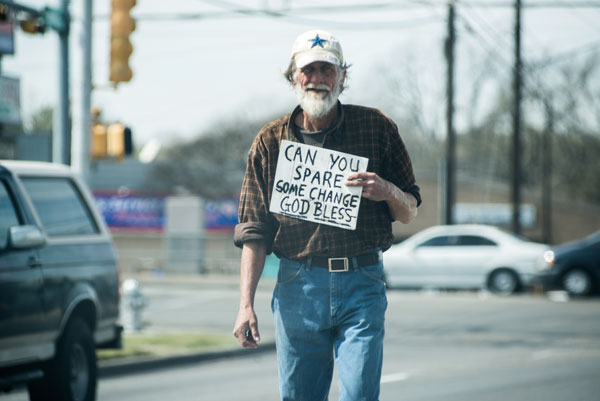 Image of a homeless man panhandling on the corner of Lamar and Rundberg.