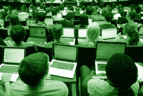 green colored photo of students using laptops in lecture hall