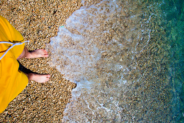 feet of person standing at the edge of the ocean, near a wave