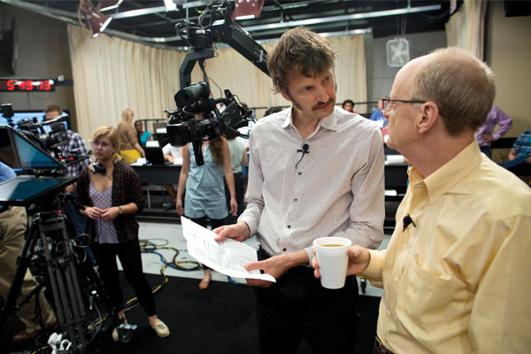 Professors Sam Gosling and Jamie Pennebaker discuss the script before the broadcast begins. Photo: Tamir Kalifa