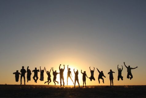 People jumping up in the air silhouetted by the setting sun in Botswana. Photo courtesy of Botswana Study Abroad Program.