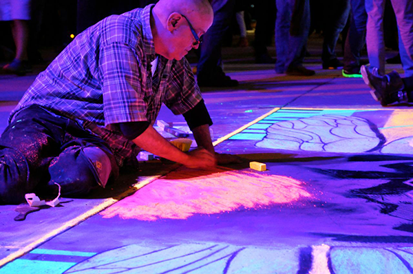 An attendee draws with chalk at an official Interactive after party.
