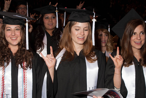 graduating students holding up hook em horns
