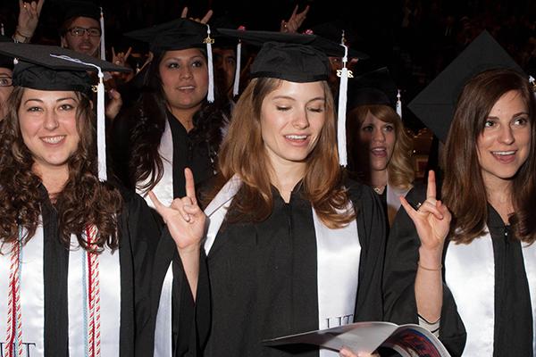graduating students holding up hook em horns