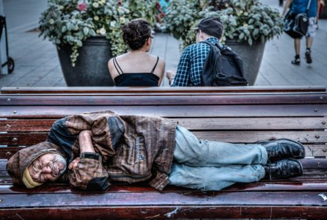 homeless man sleeping on bench opposite a couple