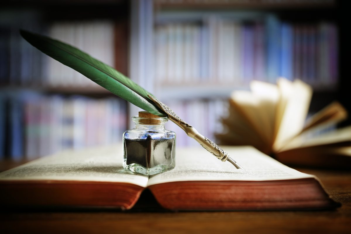 Quill pen and ink well resting on an old book in a library.