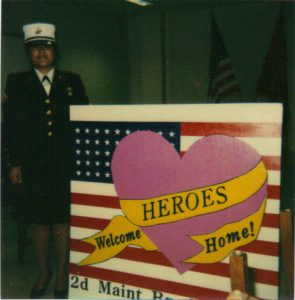 Parrish next to a welcoming sign she painted for troops coming home from Desert Storm.