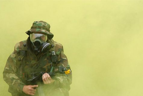 U.S. soldier practices donning his gas mask during a field exercise.
