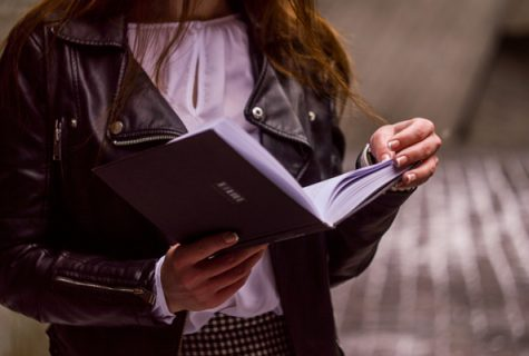Women in leather jacket holding open book.