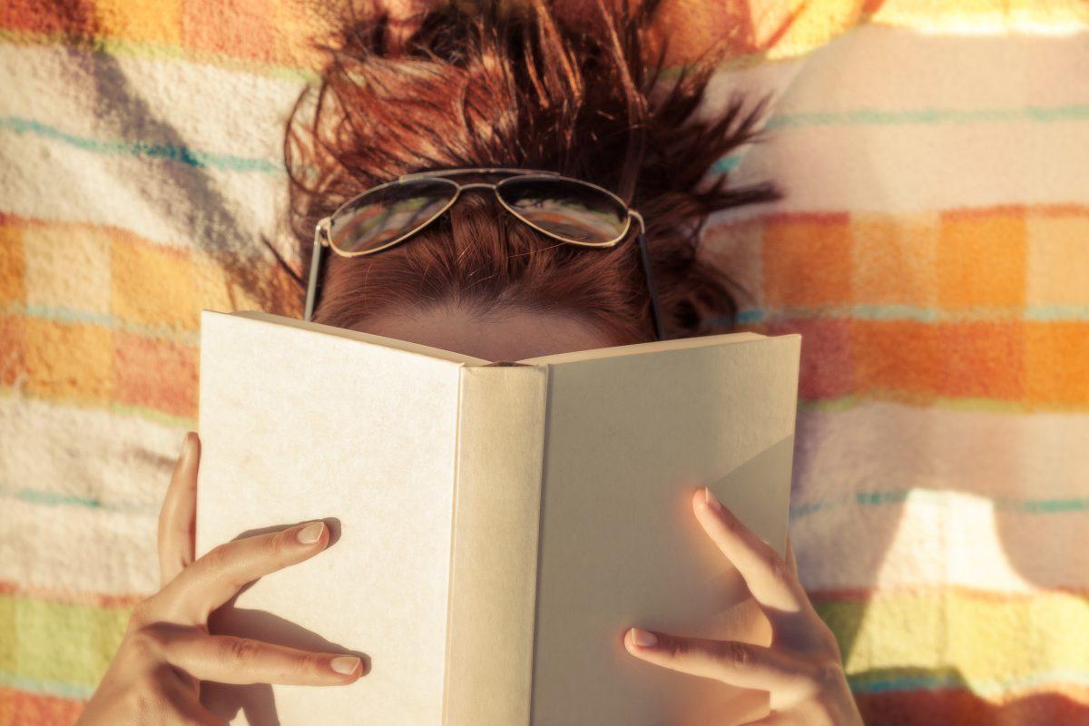 Woman with sunglasses with book covering her face.